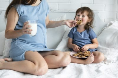gravida-mae-filha-comer-chocolate-biscoitos_23-2148252636